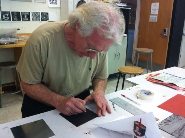 Photograph of master printer Scip Barnhart demonstrating the etching process taken by Brooke Rosenblatt.