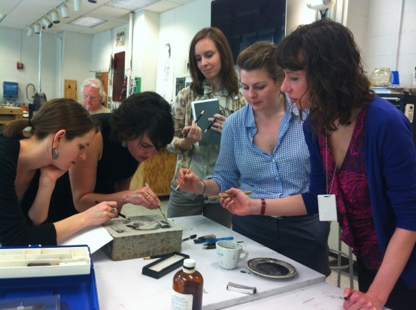 Photograph of Phillips educators and curators working together to create a lithograph taken by Brooke Rosenblatt.
