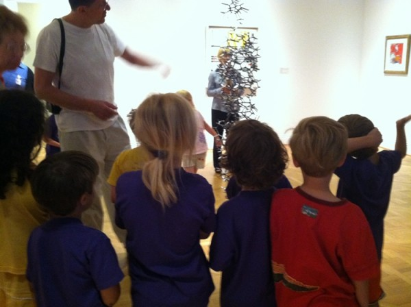 Antony Gormley and a group of children discuss his sculpture