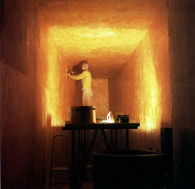 Photo of Wolfgang Laib using a warm iron to smooth the walls of the wax chamber on his own property in southern Germany. Courtesy of the artist