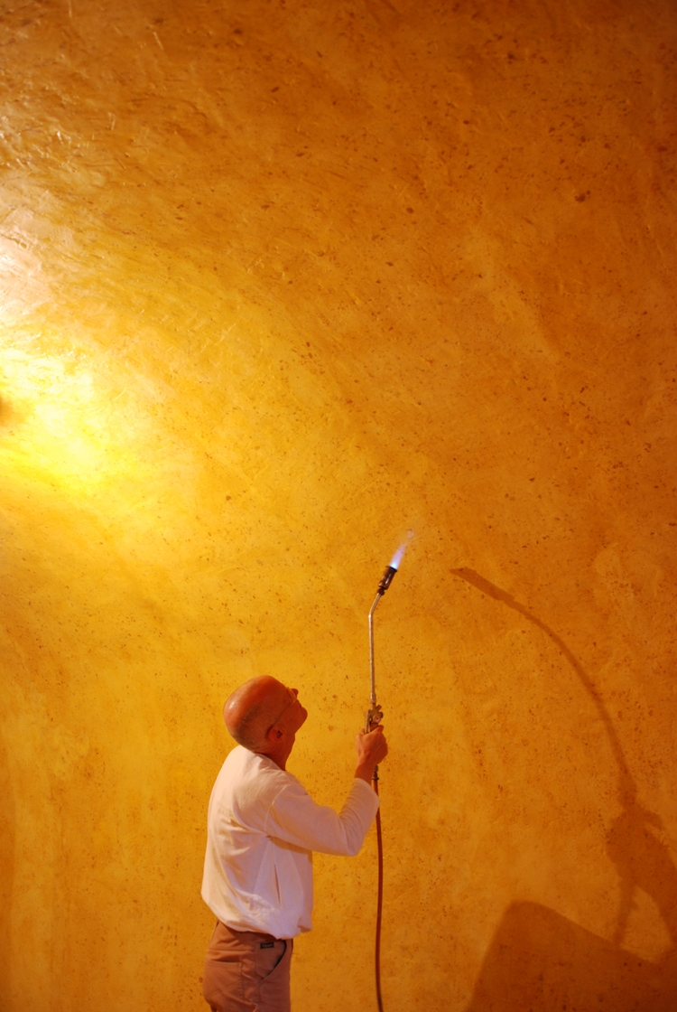 Wolfgang Laib finishes the walls of his wax rooms with a flame, which gives a unique shine to the beeswax surface. Here the artist works on a permanent wax chamber realized in a historic building in Switzerland.