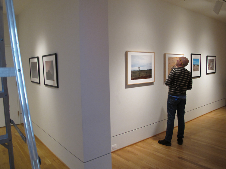 Preparator Tom Bunnell puts the finishing touches on the photo installation on the second floor. Photo: Sarah Osborne Bender