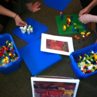 Phillips staff with bins of legos, creating sculptures