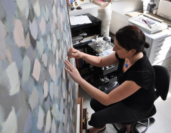 Conservator Patricia Favero holds a square of tissue against the paint surface with her left hand while, with her right hand, applying the pH-adjusted cleaning solution through the tissue using a cotton swab.