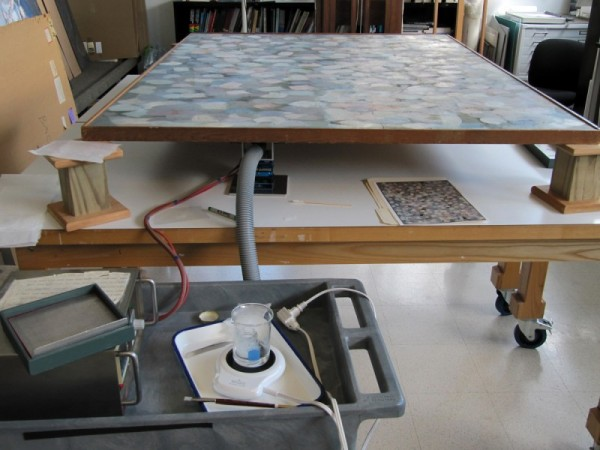 For consolidation, the 66 x 48-inch painting was placed flat and elevated on blocks.  A flat suction platen was placed underneath, against the back of the canvas (The grey hose that attaches the adjustable platen to a vacuum can be seen in the picture above).