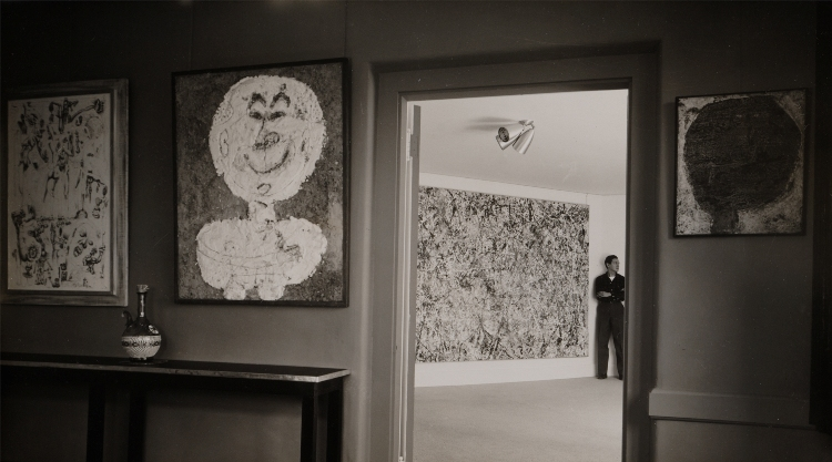 Alfonso Ossorio at the Creeks, 1952. Photograph by Hans Namuth ©1991 Hans Namuth Estate, Courtesy Center for Creative Photography. Jean Dubuffet's Francis Ponge (noir sur fond), 1947, appears at near left; Jackson Pollock's Number 1, 1950 (Lavender Mist) at center; and Dubuffet's Les Petits Yeux Jaunes, 1951, at right.