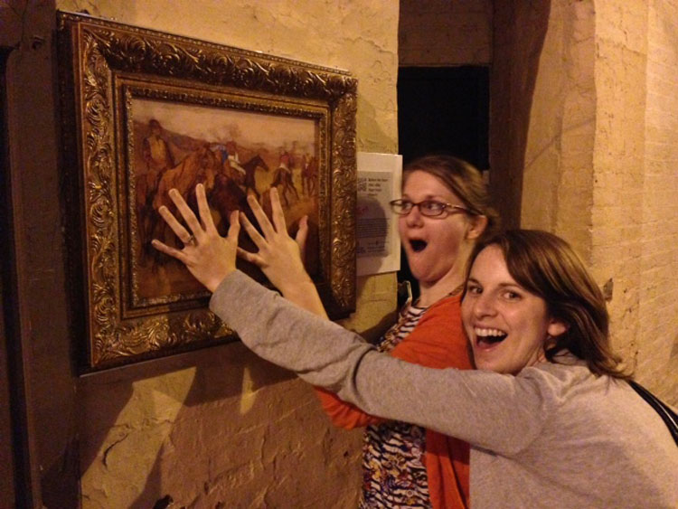 Natalie Mann and Meagan Estep excitedly palm a reproduction of Degas' Before the Race, on display on a street in Baltimore, via The Walters Art Museum. Photo: Margaret Collerd
