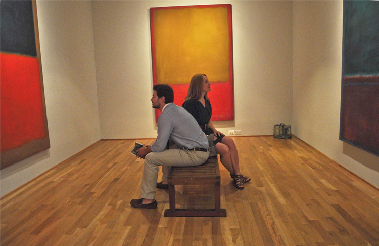 Two visitors sit on a bench in the middle of the Rothko Room at the Phillips
