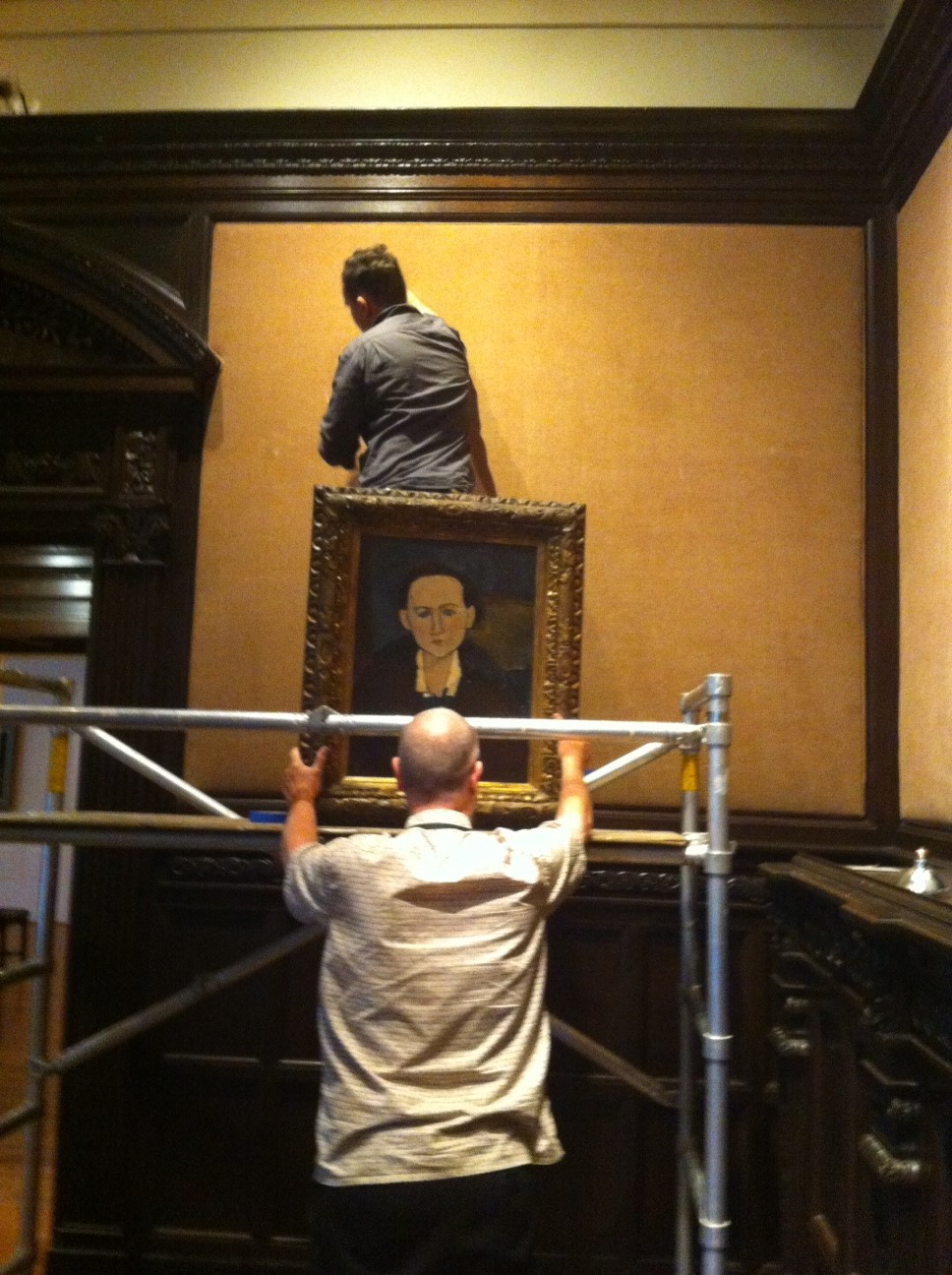 Preparators Alec MacKaye and Bill Koberg install works