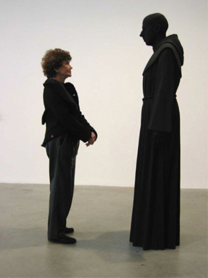 Anita Reiner standing in front a human figure cloaked in black.