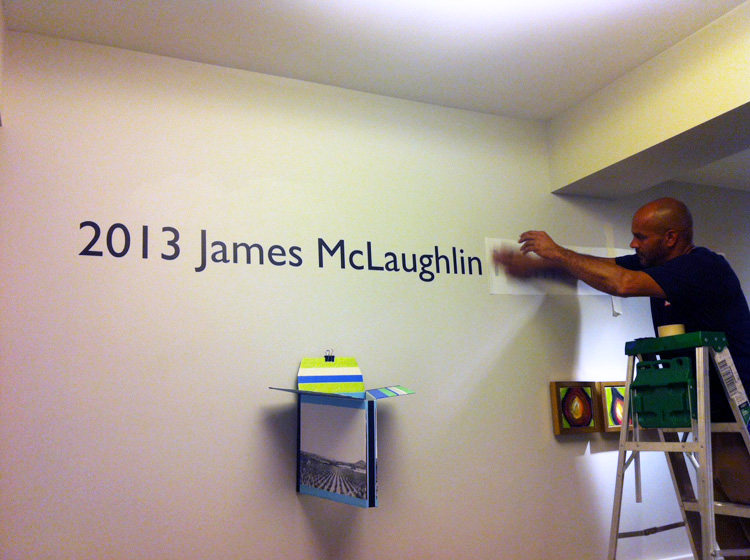 A Phillips preparator installs the title wall of the staff show.