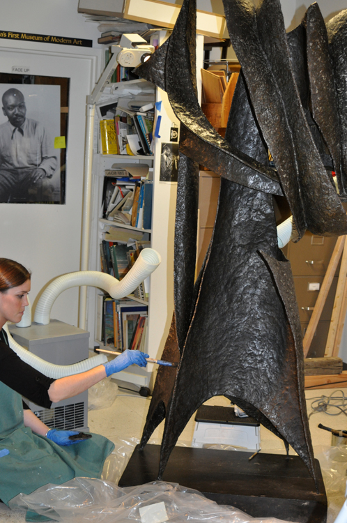 "After cleaning, applying wax to the surface of ""Ancestor"" (1958), by Seymour Lipton."