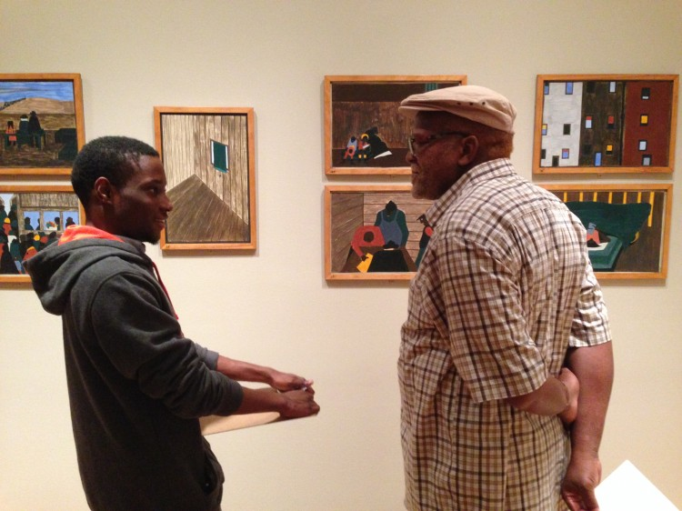A student asks an elder about his life while looking at The Migration Series.  Photo: Andrea Kim Taylor