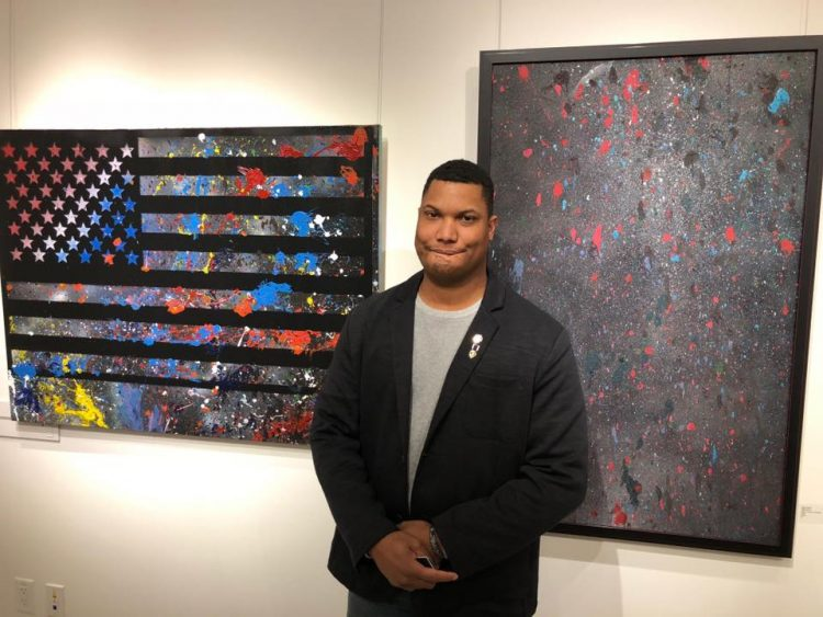 Photo of Zach Herrick with two pieces of artwork created through American Heroes HeART