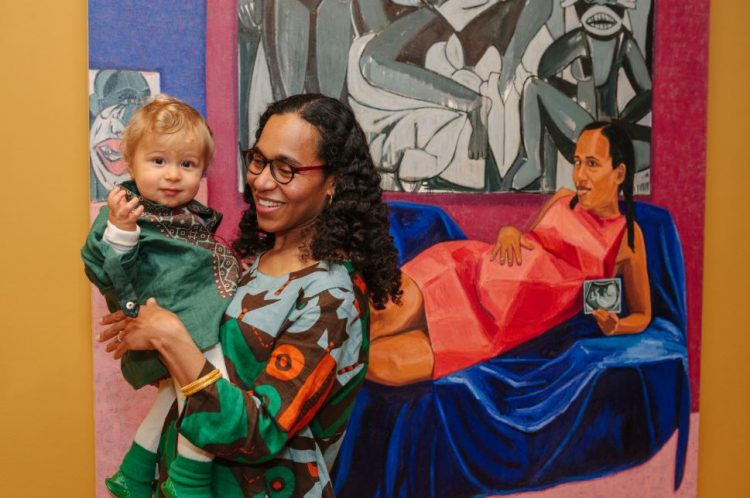 Photograph of Mequitta Ahuja holding her son in front of her painting Xpect
